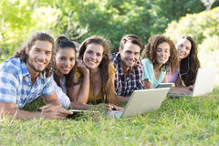 Smiling friends in the park using tablet pc and laptop Stock Photo