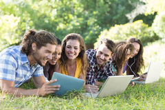 Smiling friends in the park using tablet pc and laptop. On a sunny day Stock Photos
