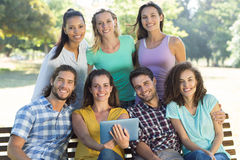 Smiling friends in the park using tablet pc Stock Photography