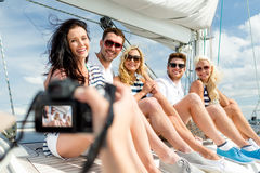 Smiling friends photographing on yacht Royalty Free Stock Photography