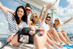 Smiling friends photographing on yacht Stock Photos