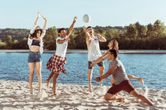 Smiling friends playing beach volleyball on riverside at daytime Royalty Free Stock Photos