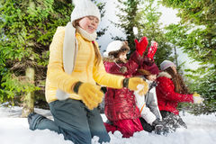 Smiling friends playing with snow in winter woods Royalty Free Stock Photo