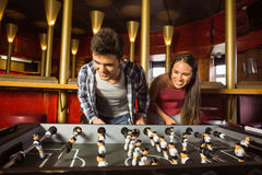 Smiling friends playing table football together Stock Images