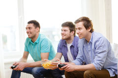 Smiling friends playing video games at home. Friendship, technology, games and home concept - smiling male friends playing video games at home royalty free stock photos