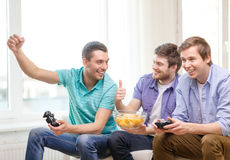 Smiling friends playing video games at home. Friendship, technology, games and home concept - smiling male friends playing video games at home stock photo