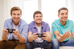 Smiling friends playing video games at home Royalty Free Stock Images