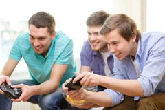 Smiling friends playing video games at home Royalty Free Stock Image