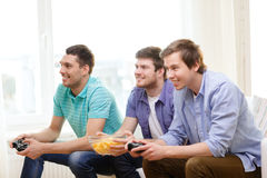 Smiling friends playing video games at home. Friendship, technology, games and home concept - smiling male friends playing video games at home royalty free stock photo