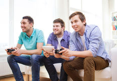 Smiling friends playing video games at home Royalty Free Stock Photography
