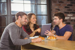 Smiling friends pointing and looking at tablet Stock Photography