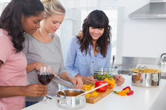 Smiling friends preparing a meal together Stock Images