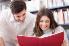 Smiling friends reading a book Royalty Free Stock Image