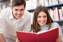 Smiling friends reading a book Stock Photo