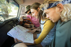 Smiling friends reading map in camper van Royalty Free Stock Photos