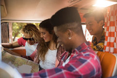 Smiling friends reading map in camper van Stock Photo
