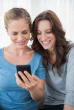 Smiling friends reading message on their phone Stock Photo