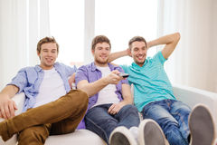 Smiling friends with remote control at home Royalty Free Stock Photo