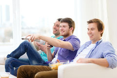 Smiling friends with remote control at home Stock Image