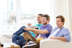 Smiling friends with remote control at home Stock Photos