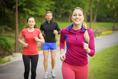 Smiling friends running outdoors Royalty Free Stock Photos
