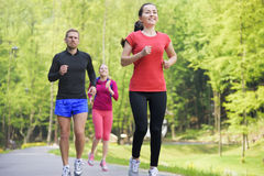 Smiling friends running outdoors Royalty Free Stock Photography