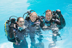 Smiling friends on scuba training in swimming pool cheering at camera Royalty Free Stock Images