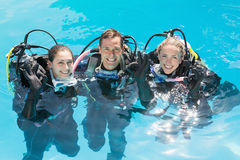 Smiling friends on scuba training in swimming pool looking at camera Stock Photos