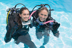 Smiling friends on scuba training in swimming pool making ok sign Stock Image