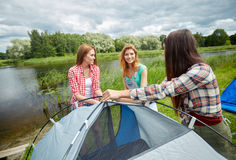 Smiling friends setting up tent outdoors Stock Images