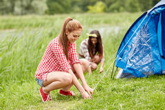 Smiling friends setting up tent outdoors Royalty Free Stock Image