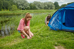 Smiling friends setting up tent outdoors Royalty Free Stock Photo