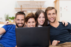 Smiling friends sharing a laptop computer Royalty Free Stock Images