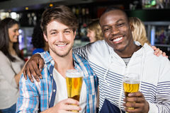Smiling friends showing beer with their friends Royalty Free Stock Photos