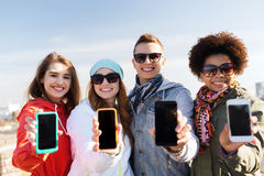 Smiling friends showing blank smartphone screens Stock Images