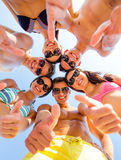 Smiling friends showing thumbs up in circle. Friendship, summer vacation, holidays, gesture and people concept - group of smiling friends wearing swimwear Royalty Free Stock Photo