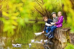 Smiling friends sit putting paper boats on pond Stock Photos