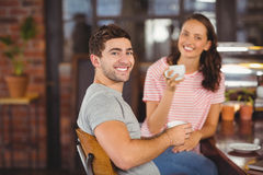 Smiling friends sitting and drinking coffee Royalty Free Stock Photo