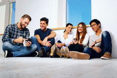 Smiling friends sitting on the floor. Portrait of a smiling friends sitting on the floor and looking at smartphone Royalty Free Stock Image