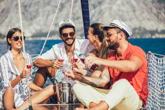 Smiling friends sitting on sailboat deck and having fun. Vacation, travel, sea, friendship and people concept royalty free stock images