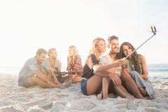 Smiling friends sitting on sand singing and taking selfies Stock Photo