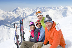 Smiling friends sitting with skis in snow Stock Photos
