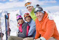 Smiling friends sitting with skis in snow Stock Images