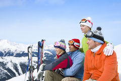 Smiling friends sitting with skis in snow Stock Photography