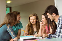 Smiling friends sitting studying together Royalty Free Stock Photos