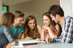 Smiling friends sitting studying together Stock Photography