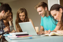 Smiling friends sitting studying and using laptop Royalty Free Stock Photos