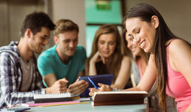 Smiling friends sitting studying and using tablet pc Stock Images