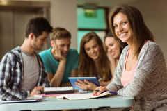 Smiling friends sitting studying and using tablet pc Royalty Free Stock Photos