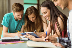 Smiling friends sitting studying and using tablet pc Stock Photography